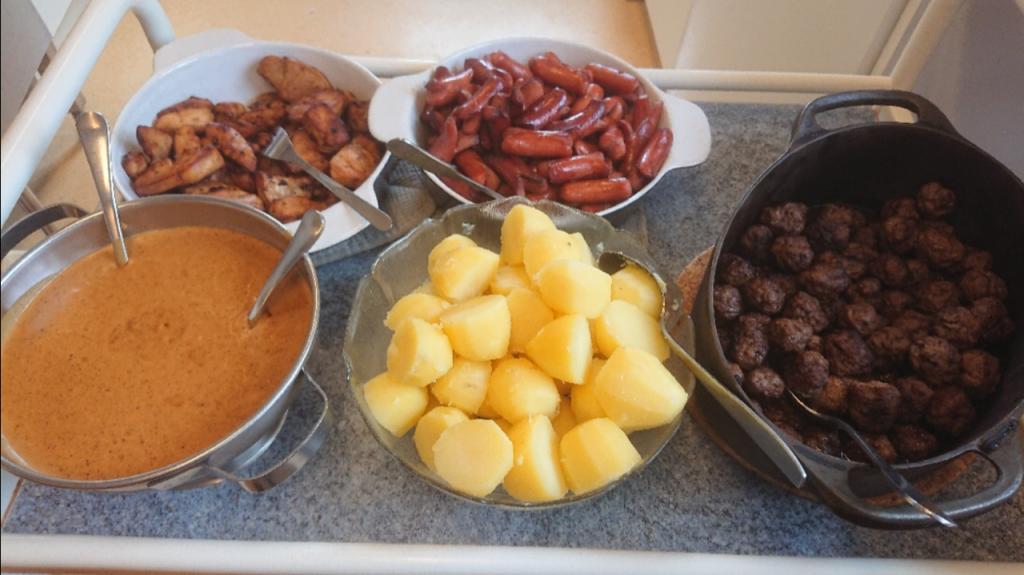 Påsklunch, köttbullar, korv, potatis och sås.