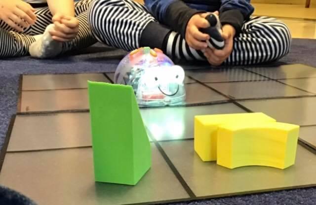 Barn vid en matta med klossar och en programmerbar robotmus